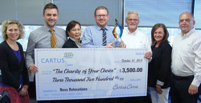 Nuss employees holding a giant Cartus Cares giant cheque and trophy