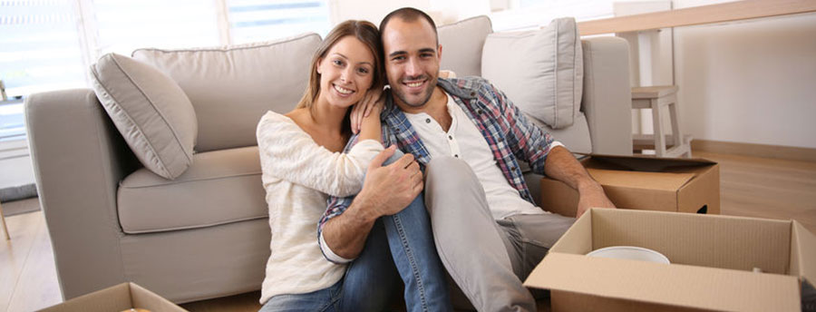 Young couple sitting on floor with moving boxes