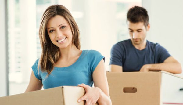young couple packing boxes for moving overseas