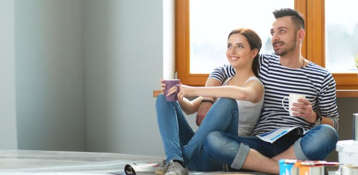 Young couple sitting on floor after moving house