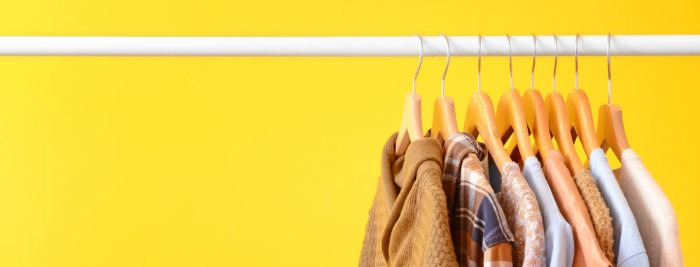 Rack with hanging clothes on color background